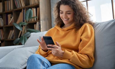 A woman sits scrolling through femtech apps in a yellow jumper and jeans on a couch