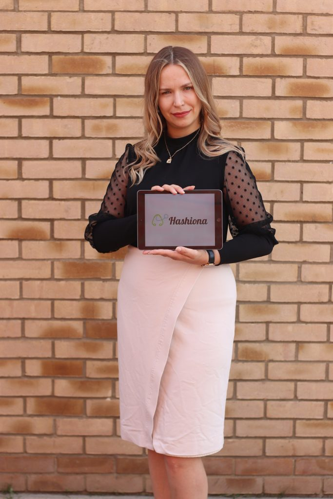 A woman in a black top and pink skirt holding a tablet