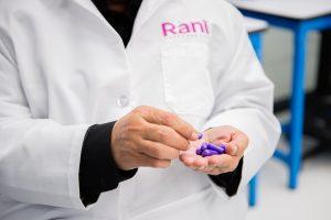 A person in a Rani Therapeutics lab coat counts purple capsules
