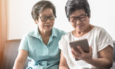 Two elderly people watching a tablet
