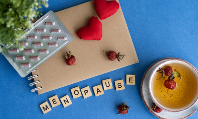 Menopause: A packet of red pills on a notepad next to a cup of herbal tea with red flowers on a blue background. There is a green plant to the left while scrabble tiles spell out menopause