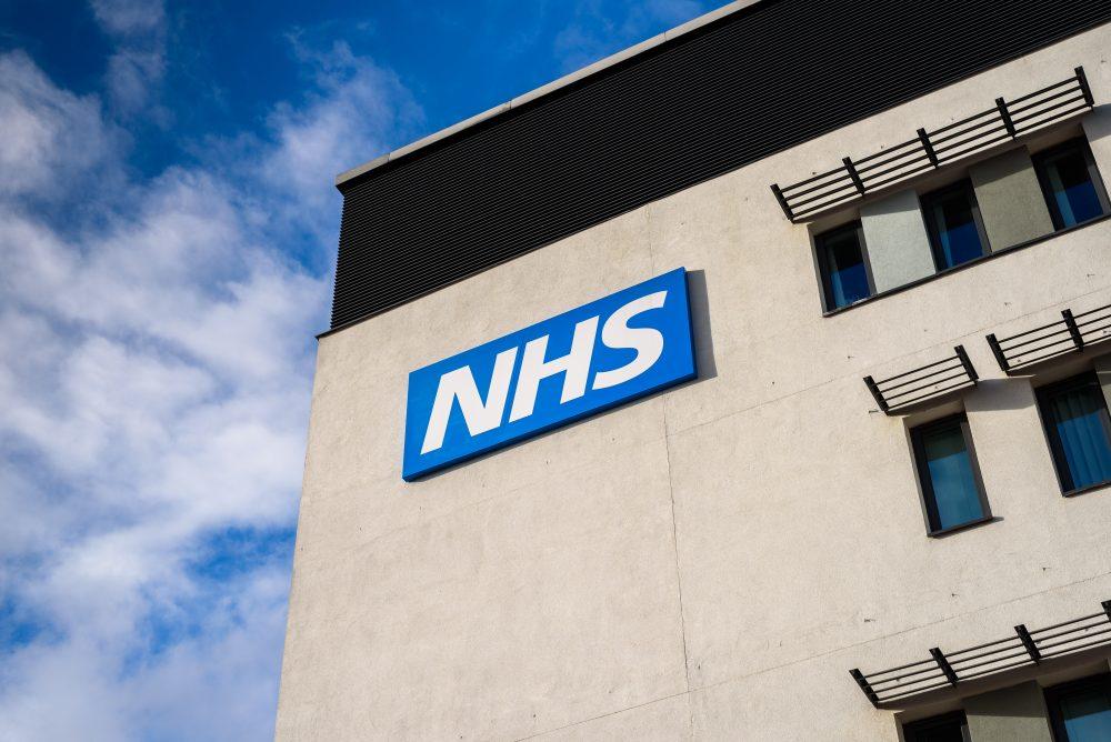 An NHS building against a blue